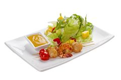 Skewers of scallops and shrimp. On a white plate royalty free stock photo