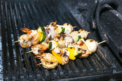 Skewers of seafood grilling Stock Photography