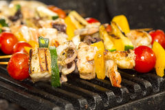Skewers of seafood grilling Royalty Free Stock Photography