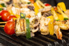 Skewers of seafood grilling Stock Image