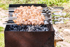 Skewers with shish kebabs on brazier on backyard Royalty Free Stock Photo