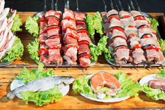 Skewers of shishkebabs and raw fish for grill Royalty Free Stock Images