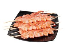 Skewers of shrimp on a black plate Royalty Free Stock Photos