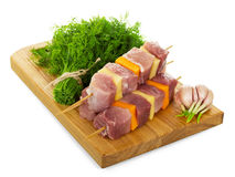 Skewers with slices fresh pork, vegetables, dill and board isolated. Royalty Free Stock Photos
