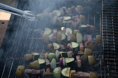 Skewers with slices of potatoes, zucchini, bacon, mushrooms, onion, kohlrabi grilled over the charcoals on barbecue grill Royalty Free Stock Photos
