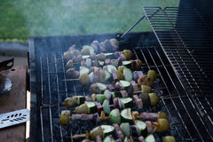 Skewers with slices of potatoes, zucchini, bacon, mushrooms, onion, kohlrabi grilled over the charcoals on barbecue grill Royalty Free Stock Images