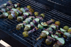 Skewers with slices of potatoes, zucchini, bacon, mushrooms, onion, kohlrabi grilled over the charcoals on barbecue grill Royalty Free Stock Photo