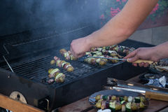 Skewers with slices of potatoes, zucchini, bacon, mushrooms, onion, kohlrabi grilled over the charcoals on barbecue grill Royalty Free Stock Image