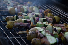 Skewers with slices of potatoes, zucchini, bacon, mushrooms, onion, kohlrabi grilled over the charcoals on barbecue grill Stock Image