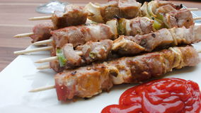 Skewers of turkey with ketchup on a white plate. Skewers of turkey on wooden sticks laid out on a white plate with ketchup stock video footage