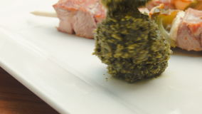 Skewers of turkey on a white plate with pesto. Pesto sauce is spread on a plate with barbecue turkey on wooden sticks stock footage