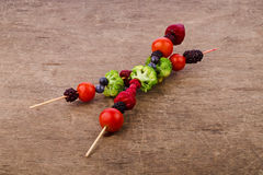 Skewers of vegetables and berries. Raspberries, broccoli, herry tomatoes, strawberry, on wooden background, healthy food, vegetarian Royalty Free Stock Photography