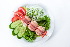 Skewers wrapped in bacon with tomatoes, cucumbers, Stock Image