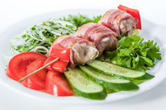 Skewers wrapped in bacon with tomatoes, cucumbers, bell peppers Royalty Free Stock Images