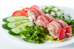 Skewers wrapped in bacon with tomatoes, cucumbers, bell peppers Royalty Free Stock Image
