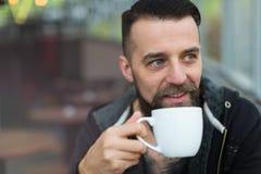 Skäggig man för barn som dricker kaffe Arkivfoto