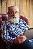 Skäggigt mansammanträde på soffan och använda minnestavlaPC Royaltyfri Fotografi