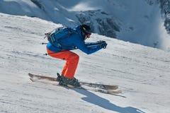 Skiër die bergaf in hooggebergte ski?en stock afbeelding