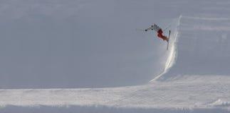 Skiër die van steile helling springt royalty-vrije stock fotografie