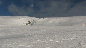 Skiër die voor de camera en de bespattende sneeuw, voorraadlengte overgaan stock video