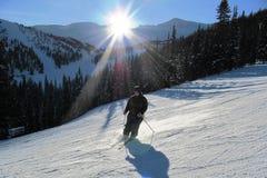 Skiër op een piste onder een het plaatsen zon Stock Fotografie