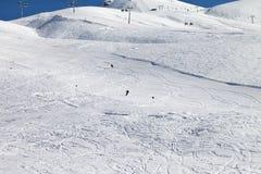 Skiërs bergaf op skihelling bij aardige zondag Stock Foto
