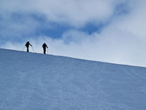Skiërs in de sneeuw tegen de horizon Stock Foto