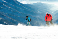 Skiërs die bergaf rit vanaf de bovenkant van een berg maken stock afbeelding