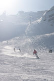 Skiërs die een helling in Alpen dalen Stock Foto's