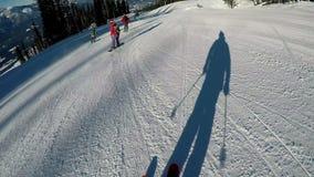 Skiërs die onderaan een sneeuwheuvel ski?en stock videobeelden