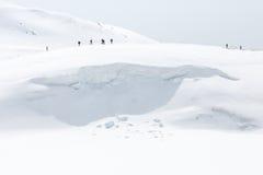 Skiërs die op sneeuw behandelde bergketens lopen Stock Fotografie