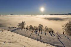 Skiërs die op zonsopgang in de bergen letten Royalty-vrije Stock Afbeeldingen