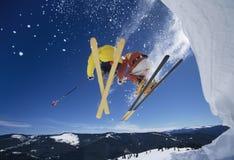 Skiërs die van Sneeuwbank lanceren die de Hellingen raken stock foto's