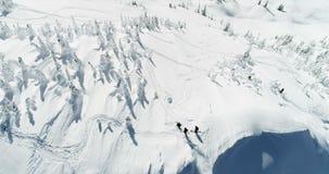 Skiërs die zich op een sneeuw afgedekte berg 4k bevinden stock videobeelden