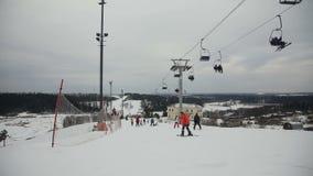 Skiërs en snowboarders die bergaf ski?en stock videobeelden