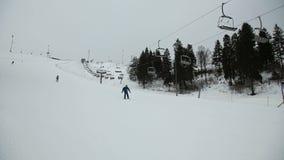 Skiërs en snowboarders die bergaf ski?en stock video