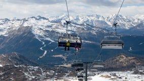 Skiërs en snowboarders die door stoeltjeslift in populaire ski reizen aangaande Royalty-vrije Stock Foto
