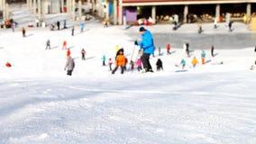 Skiërs en snowboarders die onderaan de helling gaan stock videobeelden