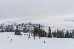 Skiërs en snowboarders die onderaan hellingen van Fluiter Blackcomb gaan Royalty-vrije Stock Afbeelding