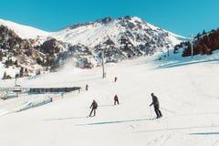 Skiërs en snowboarders die op een de bergtoevlucht van de skihelling berijden Stock Afbeelding