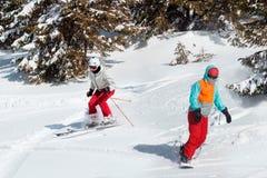 Skiërs en snowboarders die op een ski de berijden nemen op sneeuw de winterberg zijn toevlucht met sparren toneelmening als achte stock afbeeldingen