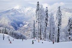 Skiërs en snowboarders die op een skihelling berijden Stock Afbeeldingen