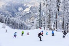 Skiërs en snowboarders die op een skihelling berijden Royalty-vrije Stock Afbeelding