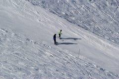 Skiërs en snowboarders die op een skihelling berijden Stock Foto