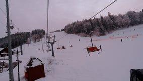Skiërs en snowboarders die op hellingen van skitoevlucht Bukovel genieten van, de Oekraïne stock footage