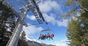 Skiërs en snowboarders op een skilift, cinematic schot Stock Afbeeldingen