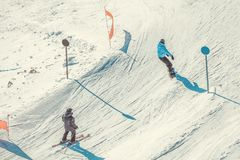 Skiërs en snownoarder bergaf het doen van rit vanaf de bovenkant van een berg stock foto