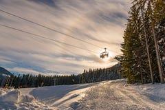 Skiërs op de skistoeltjeslift op de achtergrond van de zon en een blauwe hemel stock foto's