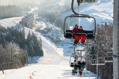 Skiërs op kabelwagen in Bukovel met snow-covered hellingen als achtergrond Stock Afbeelding
