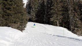 Skiërs op piste die bergaf gaan stock footage
